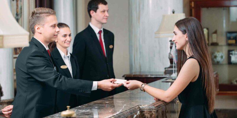 Mitarbeiter an der Rezeption im Hotel übergeben Schlüssel
